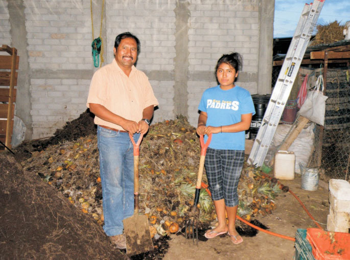 Jesús León Santos and his daughter Diana with the compost at their farm