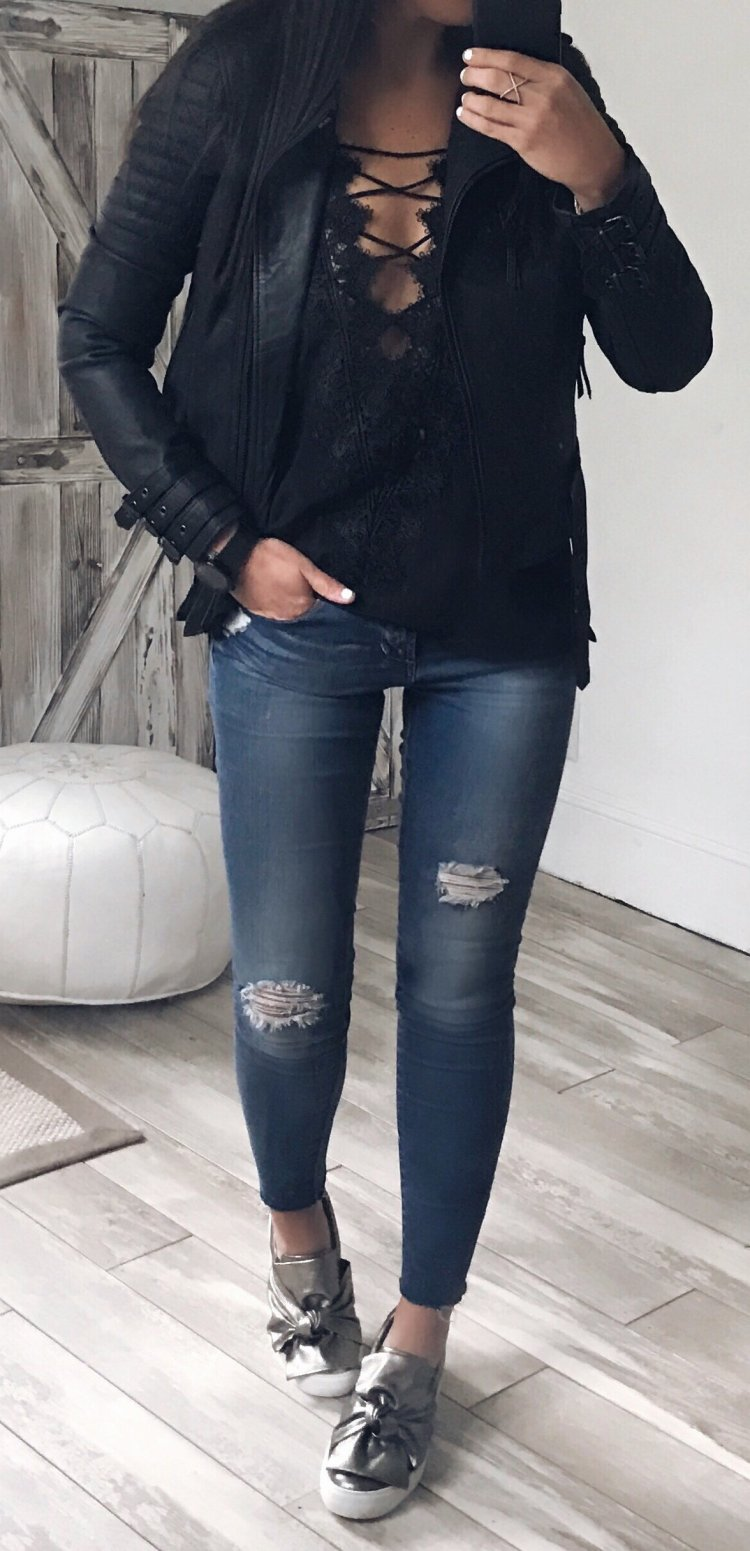 women's black full zipped leather jacket and; blue distressed jeans