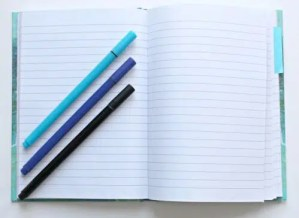 Open notebook with three pens laying diagonally at a 45 degree angle; blue, purple, black