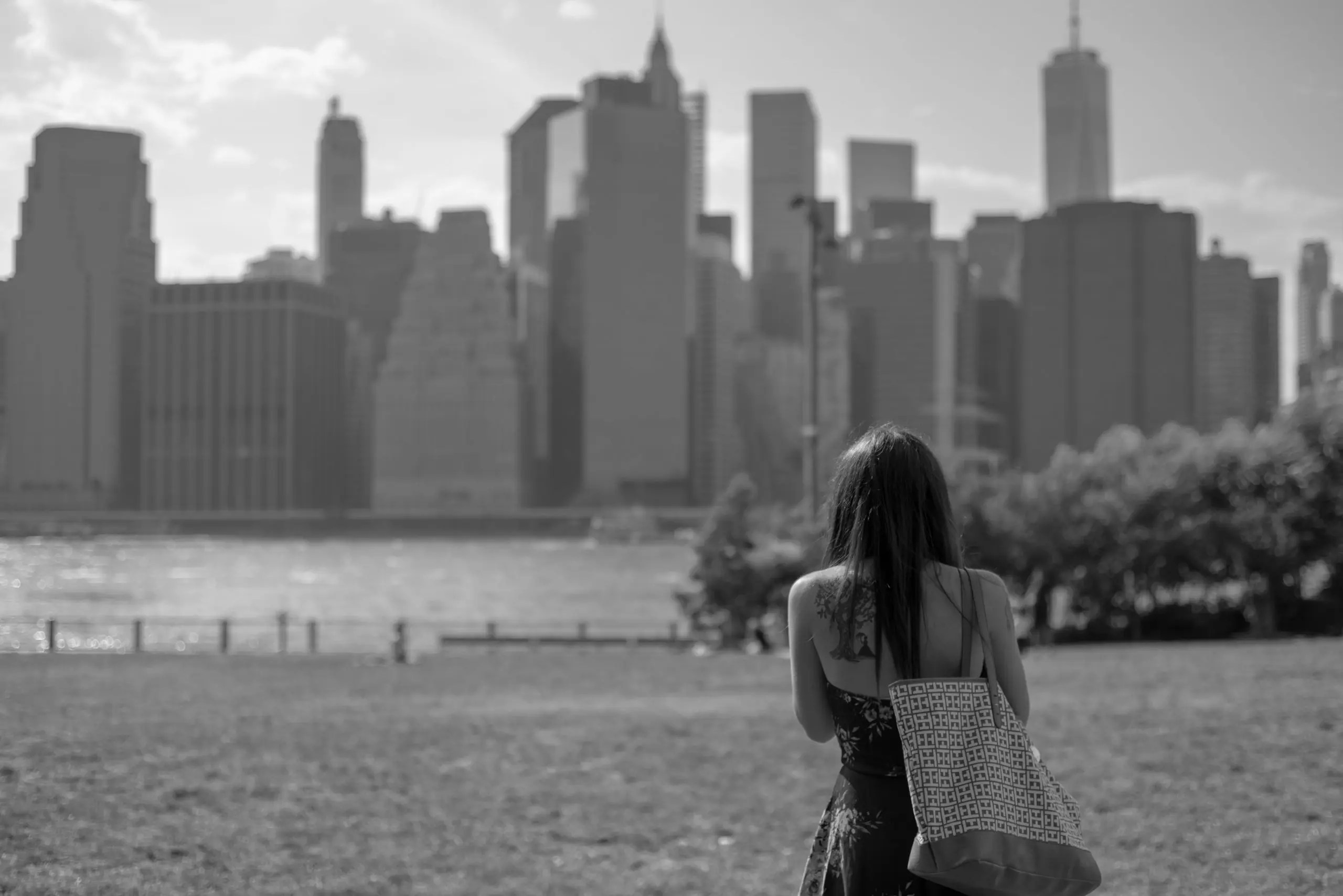 Model posts in front of the view of Downtown Manhattan from the Brooklyn side of the water. In the Background you can see the skyline of New York City.