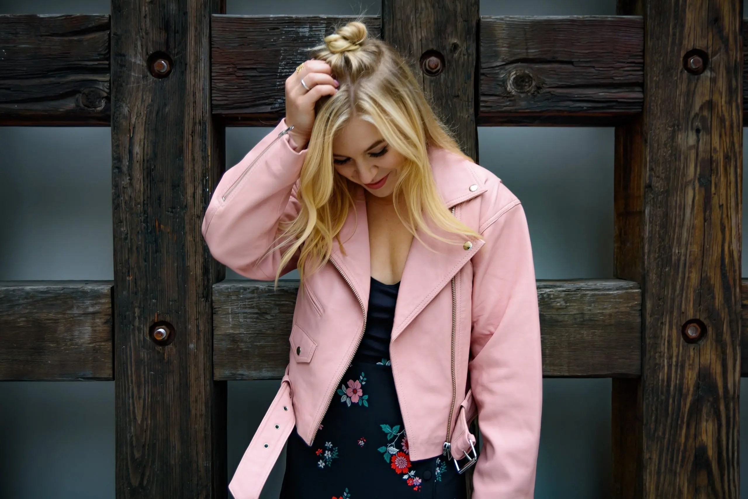 Model posing in front of wooden beams color contrasting with pink and dark blue hues of her outfit.