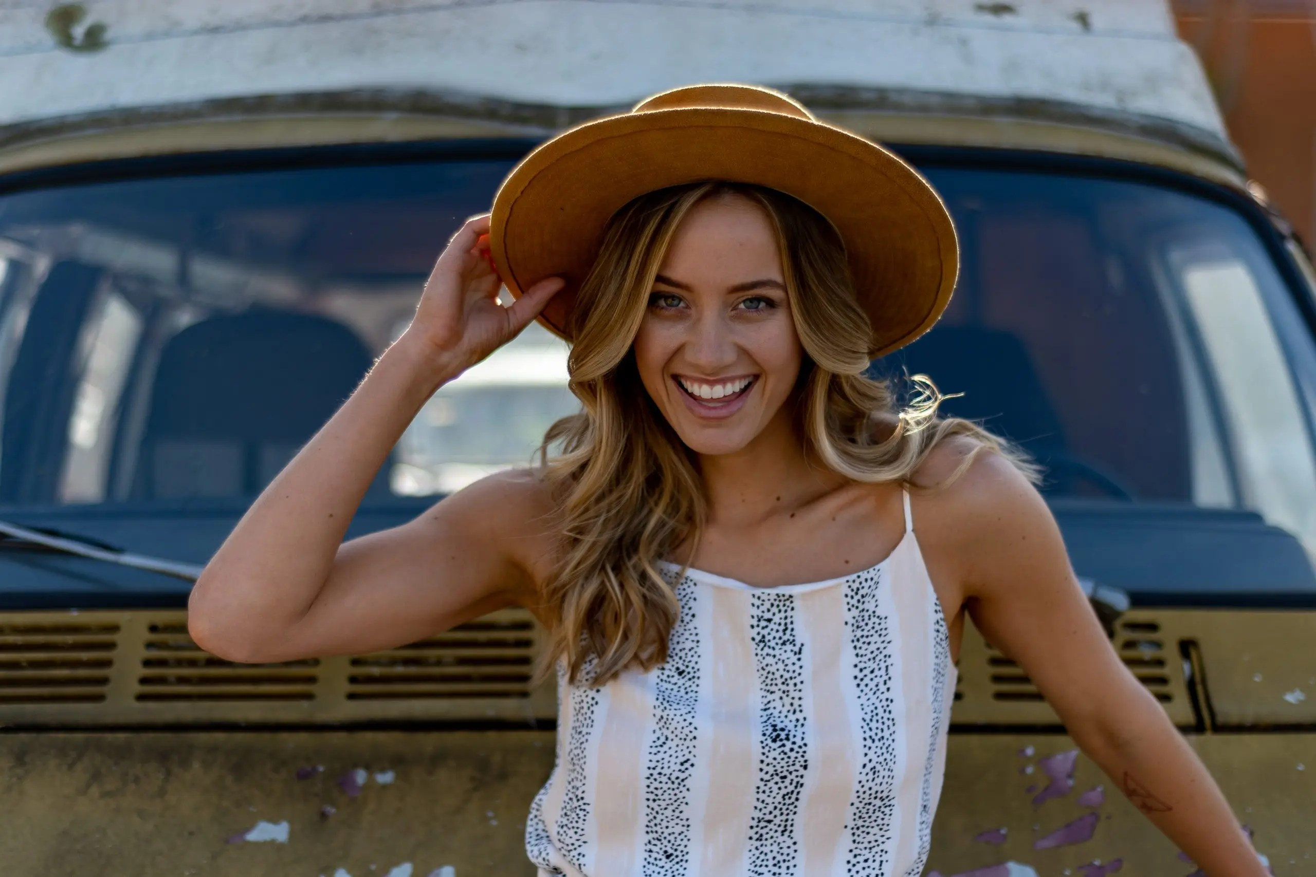 Carly Lane wearing a hat posing in front of a old school yellow van.