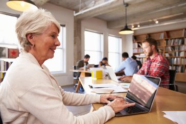 Senior Businesswoman Using Laptop At Desk In Busy Office