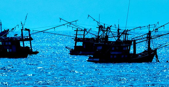 A group of 3 fishing boats in the ocean.