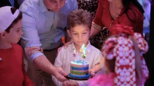 Birthday boy blows out candles