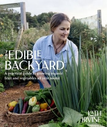 The Edible Backyard book cover with author Kath Irivne kneeling down gathering produce from her garden in a big basket while admiring her onions