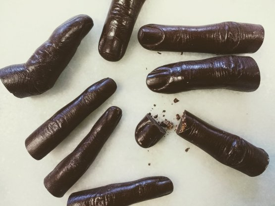 8 human fingers made out of dark chocolate on a white background one is broken