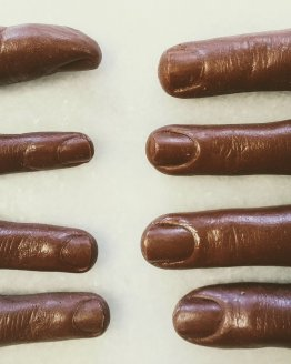 8 human fingers made out of milk chocolate on a white background