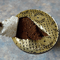 Opening the Carte Noire capsule to reveal the coffee inside.
