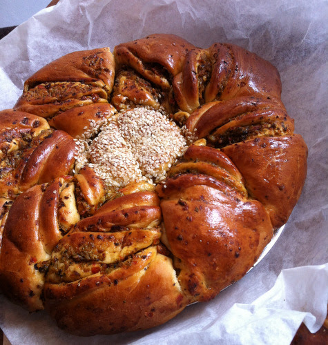 Savoury twist: This intricate looking ring was made from 3 disks of brioche dough sandwiched with a dryish mixture of peppers, olives, sun dried tomatoes and herbs. A circular cutter is placed in the centre but not used to cut. The dough sandwiches are marked into eighths, each is then twisted two or three times, glazed and left to prove. The key is to let the glaze dry out before baking. It is very delicious!