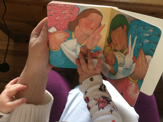 Toddler and mother reading book