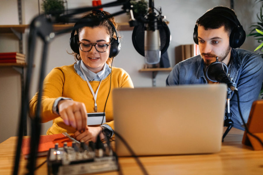 Photo of two young people making a podcast.