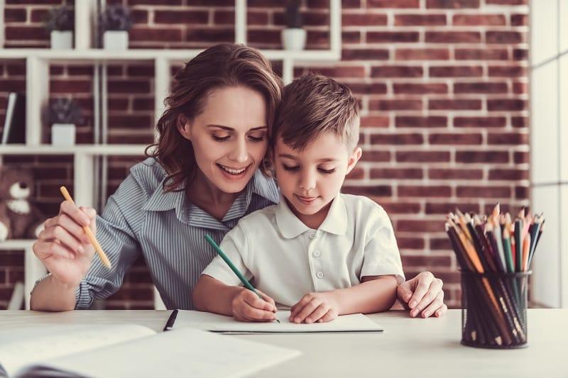 una madre o una profesora ayuda a un niño a hacer la tarea - personas con altas capacidades