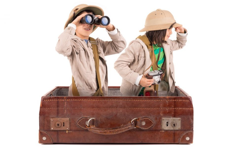 Children's couple in safari clothes playing inside a suitcase