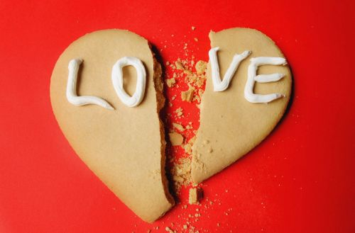 """Cookie in shape of heart with word """"love"""""""