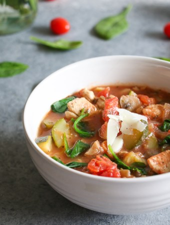 One-pot,Tuscan chicken and veggie soup in a white bowl on a gray background.