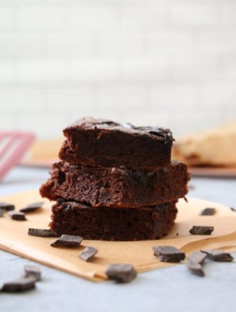 Vertical stack of three chocolate cake bars, surrounded by chocolate chips, on parchment paper with a subway tile backsplash