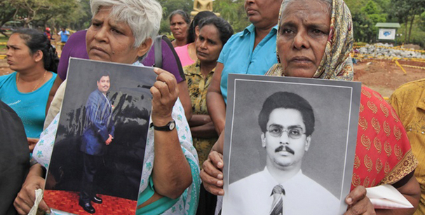 Sri Lankan Tamil women hold up photographs of their missing sons during a protest against the Sri Lankan government in Colombo