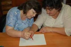 Foto de la derecha- Un profesor de apoyo y un profesor de educación regular están dibujando juntos con un lápiz. El objetivo de la actividad es provocar la autorreflexión sobre el trabajo en equipo, dirigir y seguir una directriz.