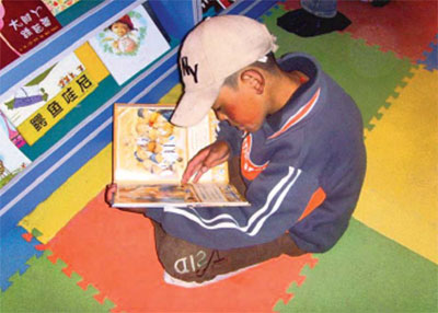A child reading a book at the language learning resource centre