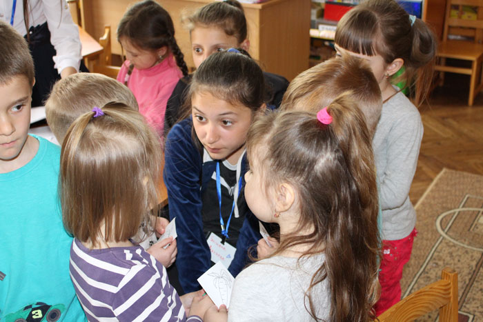 female student (young researcher) surrounded by kindergarten children. Student is listening to what a child is saying