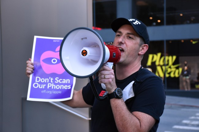 """a man wearing an eff hat and shirt holds a bullhorn and a sign reading """"don't scan our phones"""""""
