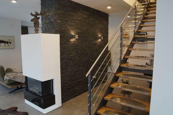 Die Treppe nach oben besteht aus Stahl, Glas und Holz und fügt sich so hervorragend in das Interieur-Design des Hauses ein. (Foto: OKAL Haus GmbH / Markus Burgdorf)