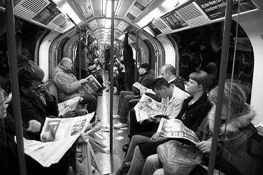 commuters on the London Underground reading their newspapers