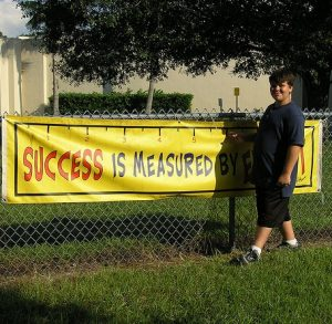 boy standing in front of a banner reading 'success is measured by...'The final word is obscured