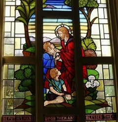 Reclaimed stained glass window for sale depicting Jesus in the garden with children.