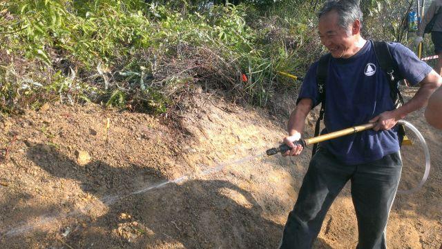彎位完工,「灑水儀式」-- 固定石牆之泥土。