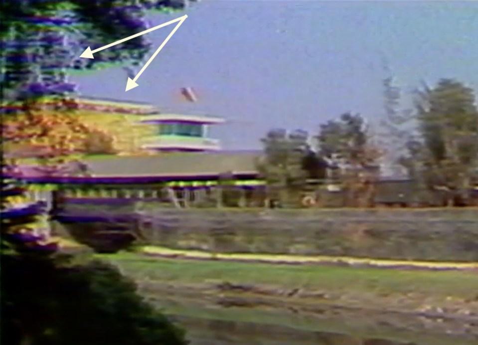 鏡頭左端有兩幢建築(被樹稍為遮住)。