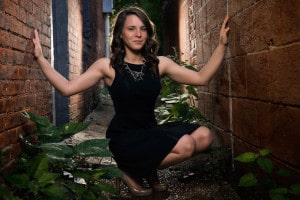 FZE Fort Zumwalt East Senior Pictures Laryssa Roeper poses in brick alley in downtown St. Charles MO in black dress with professional photographer lighting. Celebrity Style.