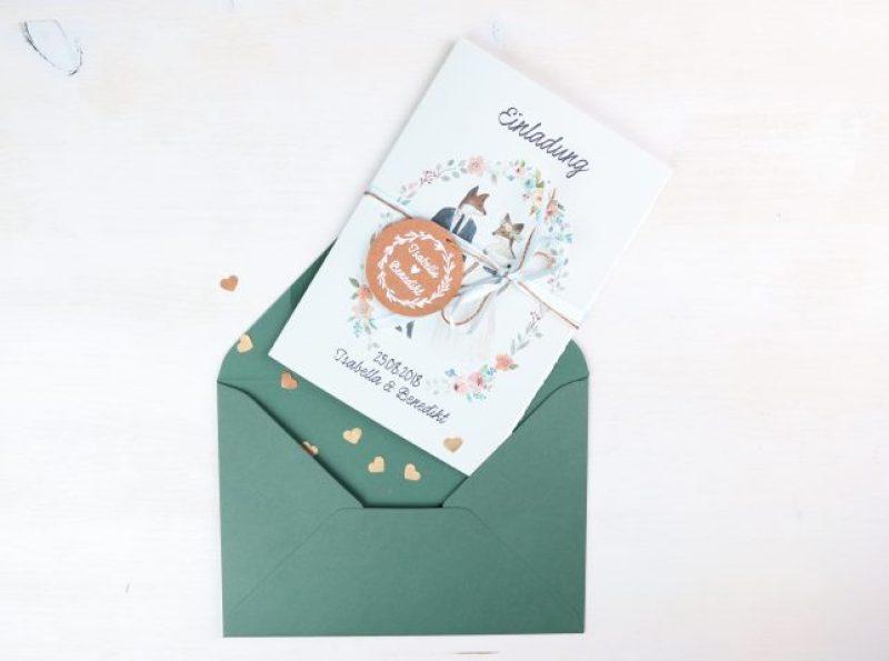 Einladungskarte mit etwas Herzchen-Konfetti im grünen Umschlag.