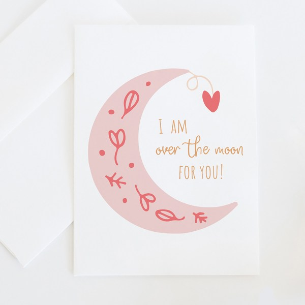 """Over The Moon    A whimsical greeting card illustrated with an illustrated moon with floral details and a whimsical hanging heart, featuring the saying """"I am over the moon for you"""". >> Eight Pepperberries Paperie"""