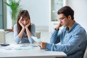 Junges Paar beim Berechnen der Schulden