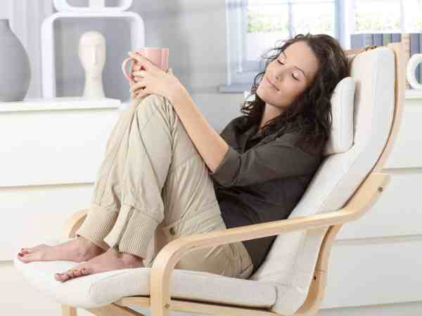 12174604 – woman relaxing with closed eyes and cup of tea in armchair at home, daydreaming.