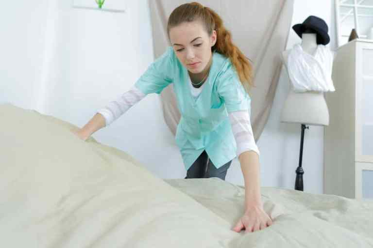 maid making bed in a nursing home