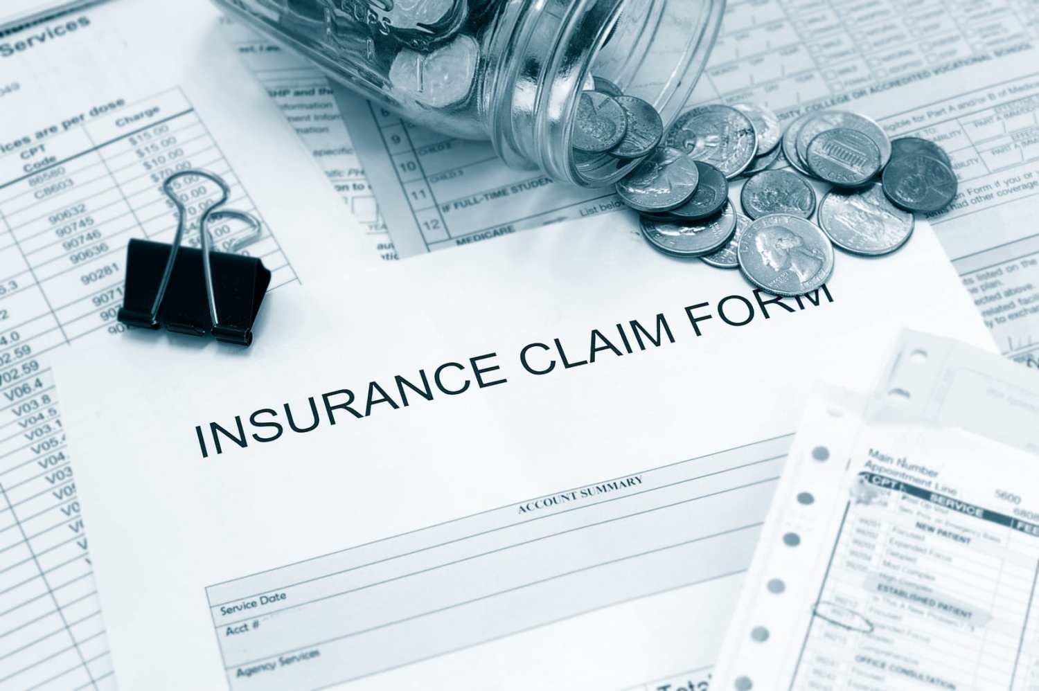Patient medical bills and claim form with coin jar