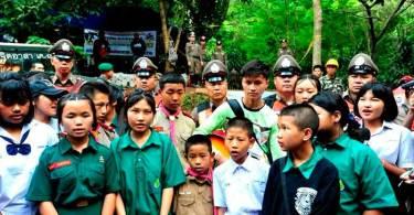 Crianças oram e louvam em frente à caverna onde meninos estão presos, na Tailândia