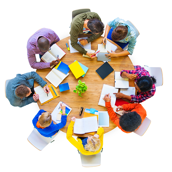 Overhead shot of several people sitting at a round table working with books and notes
