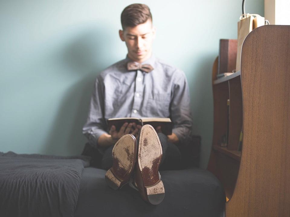 opiskelija istuu sängyllä lukemassa kirjaa