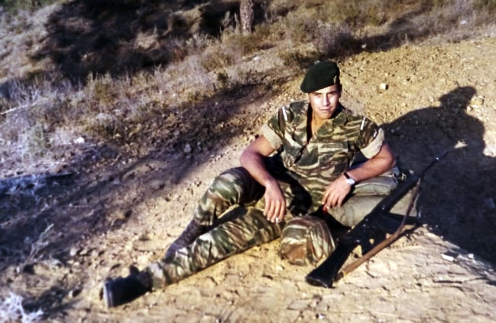 Απεικονίζεται ο Μανώλης Μπικάκης με στρατιωτική στολή καθισμένος πάνω σε ένα βουνό