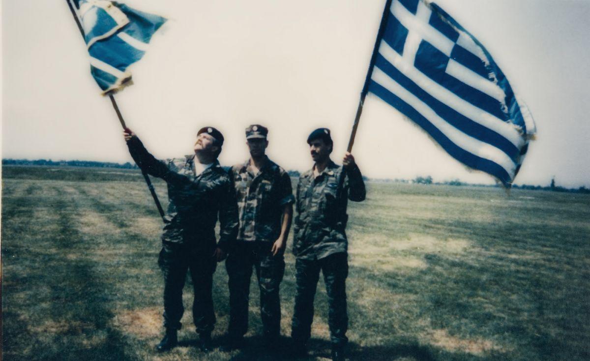 Απεικονίζονται τρεις στρατιώτες που κρατούν ελληνικές σημαίες
