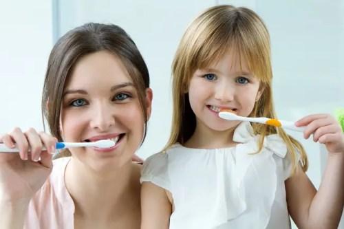 Madre e hija limpiándose los dientes