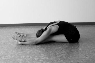 Mujer practicando postura Paschimottanasana