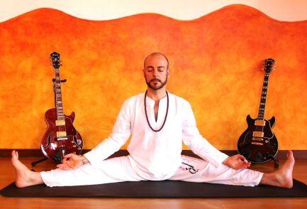 Chema Vilchez, autor de música de yoga, rodeado de guitarras y haciendo yoga.