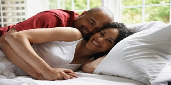 Smiling couple laying in bed