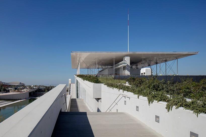 Τέσσερα χιλιόμετρα νότια του κέντρου της Αθήνας, ο Ρένζο Πιάνο ολοκλήρωσε το μεγάλο δημόσιο συγκρότημα μέσα σε έναν πάρκο 170.000 τετραγωνικών, που περιλαμβάνει την Εθνική Βιβλιοθήκη της Ελλάδας, καθώς και την Εθνική Λυρική Σκηνή. Η μεγάλη στέγη ολοκληρώνεται με 10.000 τετραγωνικά μέτρα φωτοβολταϊκών κυττάρων.