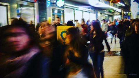 Imagen de archivo de un repartidor de Glovo en medio de la multitud.